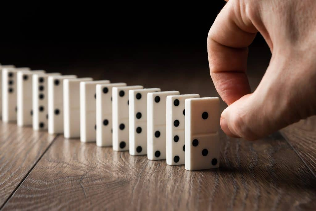 Hand pushing dominoes, indicating the ripple effect of kindness